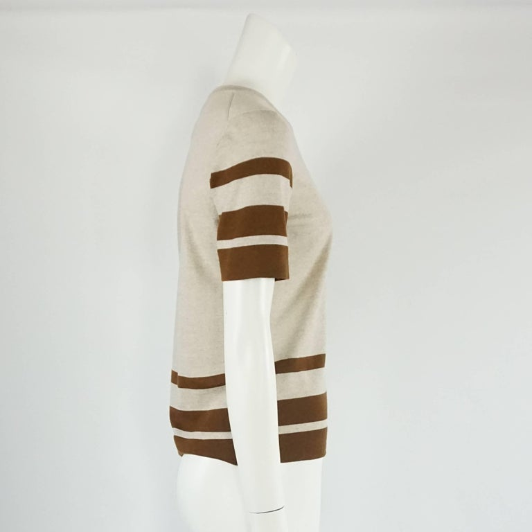 This Salvatore Ferragamo grey and brown virgin wool top has a classic-equestrian feel. The blouse is round necked with stripes on the sleeves and bottom and a small Ferragamo metal logo on the bottom. The piece is in excellent condition with a