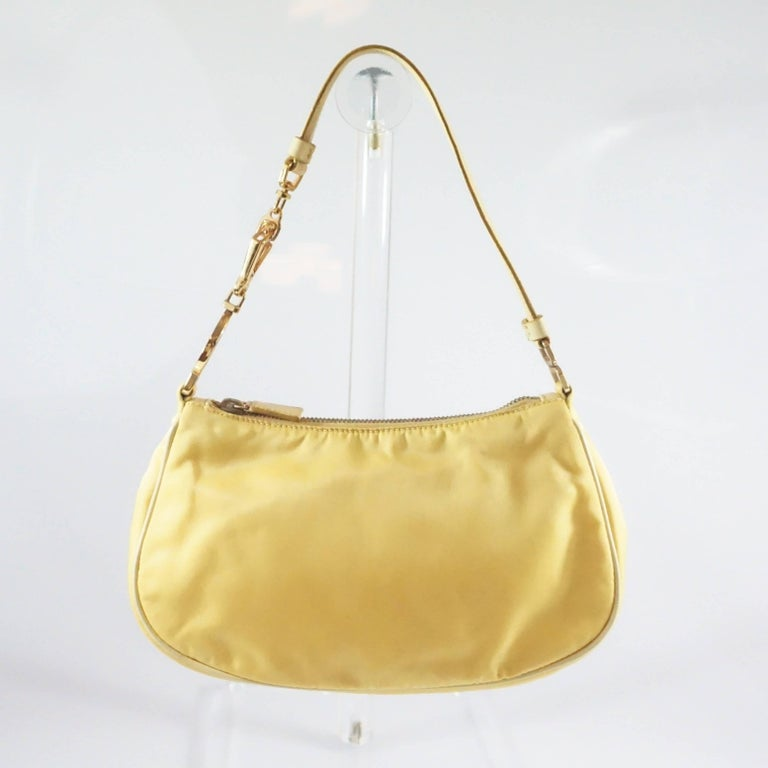 This Prada yellow baguette is made of nylon and has leather accents. The bag features the signature Prada enamel logo and a removable leather strap with gold hardware accents. The bag is in good condition with some hardware tarnishing and wear to