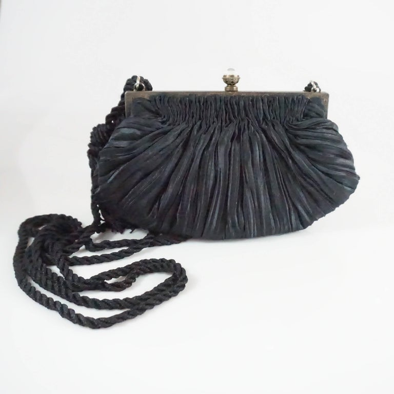This Revivals bag is made of a black plated satin fabric. The frame of the piece also has etching with an ivory and red enamel design and small graphite stones. The bag also features a push clasp, 1 small interior pocket, and a rope strap with