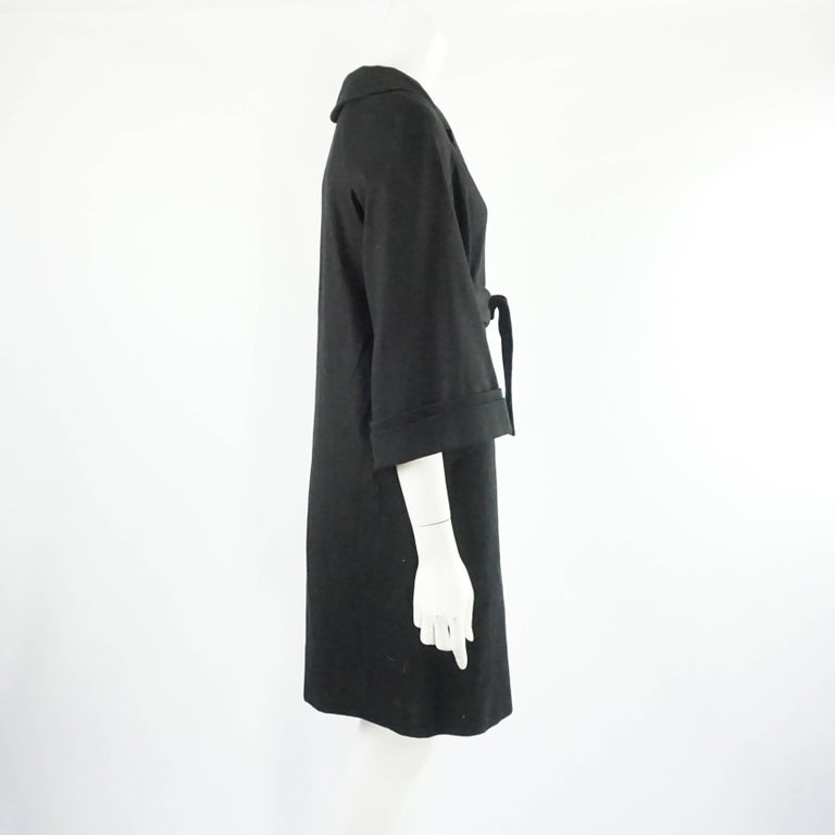 This Gucci coat is a staple and a perfect transition piece from summer to fall. The collared dress coat has buttons in the front and a tie belt, both with metal Gucci labeled accents. The sleeves are 3/4 length and the coat dress is 3/4 as well. The