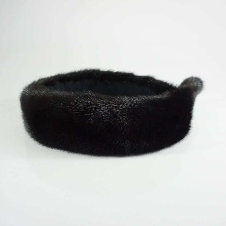This Birger Christensen dark brown mink head piece has such a rich color, it almost pasts for black. The piece sits on top of the head and has a rhinestone pendant. The piece is in excellent condition with minimal wear to the fur.