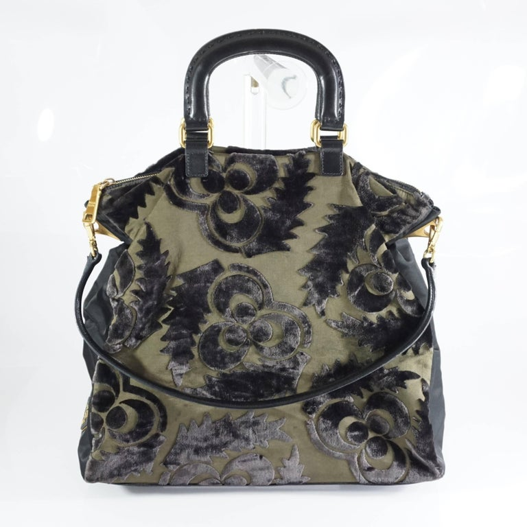 This Prada cut velvet bag is a unique piece. It features a floral velvet design, black nylon sides, black saffiano leather handles, and a shoulder strap. The bag is in good condition with a couple small blemishes on the fabric and a mark on the