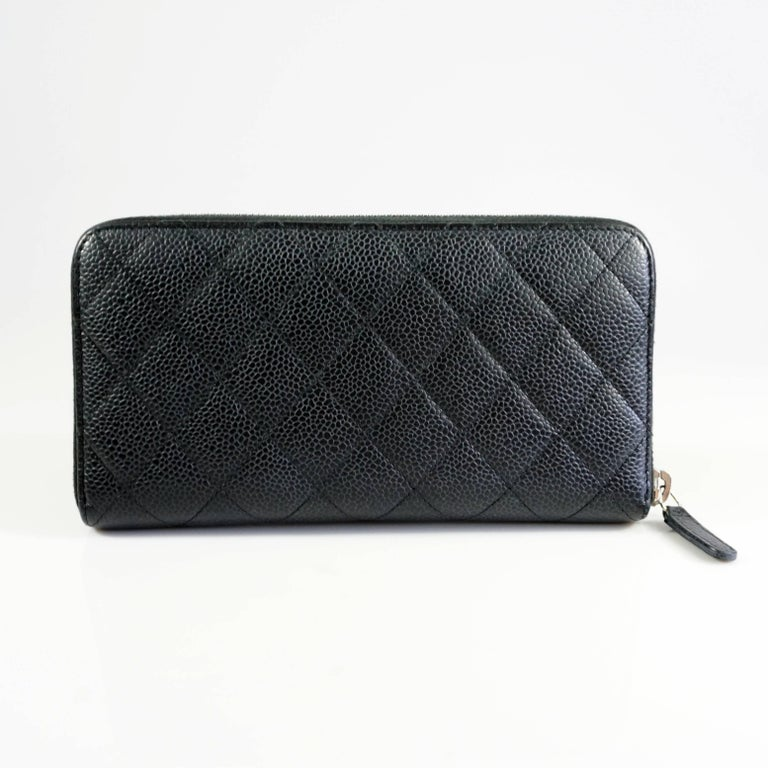 This classic Chanel wallet is black and is made of quilted caviar leather. The wallet has silver hardware and features a