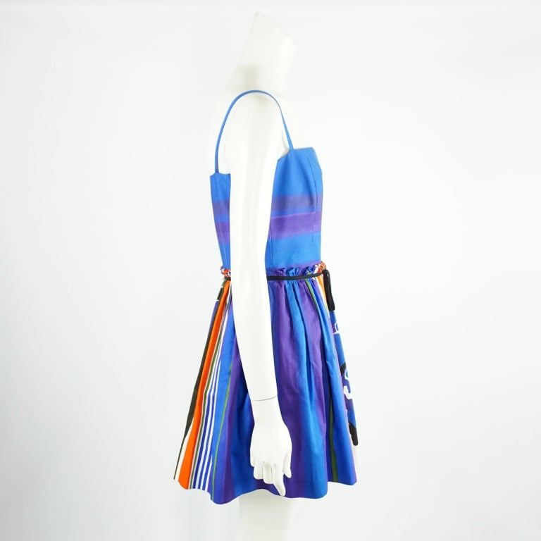 This fun Red Valentino dress has hues of red, purple, blue, green, and ivory. The dress is spaghetti strap and features a gathered waist, small bow tie belt, a silver side zipper, and 2 side pockets. The dress is in excellent condition with a couple