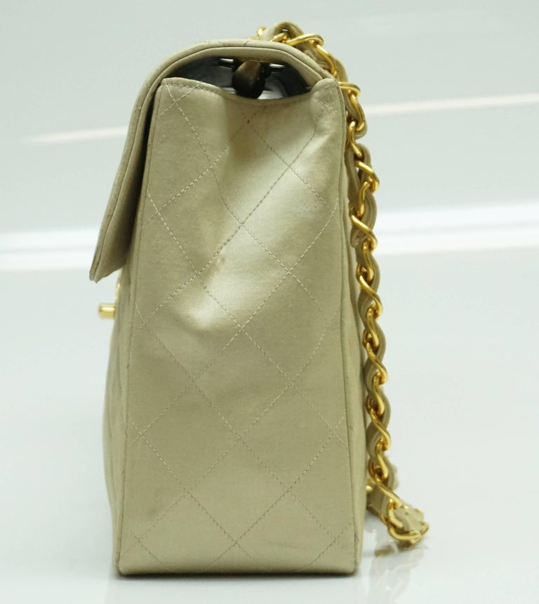 Chanel Gold Fabric Maxi Single Flap Handbag - GHW - Early 90's  This classic chanel handbag is in a very unique light gold fabric. The inside is fully leather. It has gold hardware. It has a minor chip/peel area in the CC and therefore we priced it