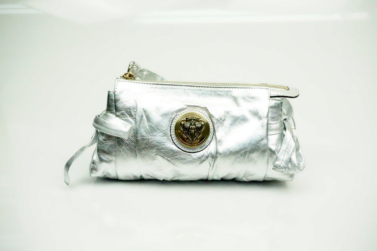 Gucci Silver Metallic Leather Clutch  This beautifulclutch is in excellent condition. The bag has two bows on the sides of the clutch. The zipper is a gold tone and has a wrist strap attached to it. There is also a gold Gucci logo on the center