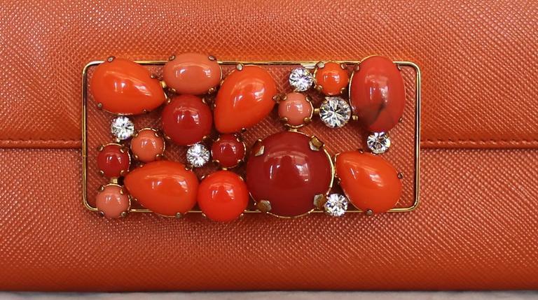Prada Orange Saffiano Wallet w/ Multi-Tone Enamel Orange Stones & Rhinestones GHW.  It is in excellent condition.  Beautiful orange saffiano exterior and interior.  It has stunning unique multi-tone orange enamel stones and rhinestones on the front.
