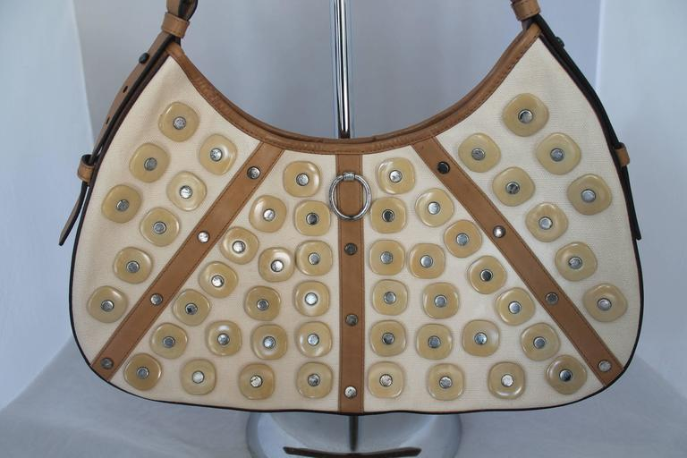 Yves Saint Laurent Beige Canvas Shoulder Bag w/ Enamel & Silver Studs. It also has luggage color and leather trim and handle. This bag is in fair condition. It has staining on the back of the bag, the paint on the silver studs is chipped, the