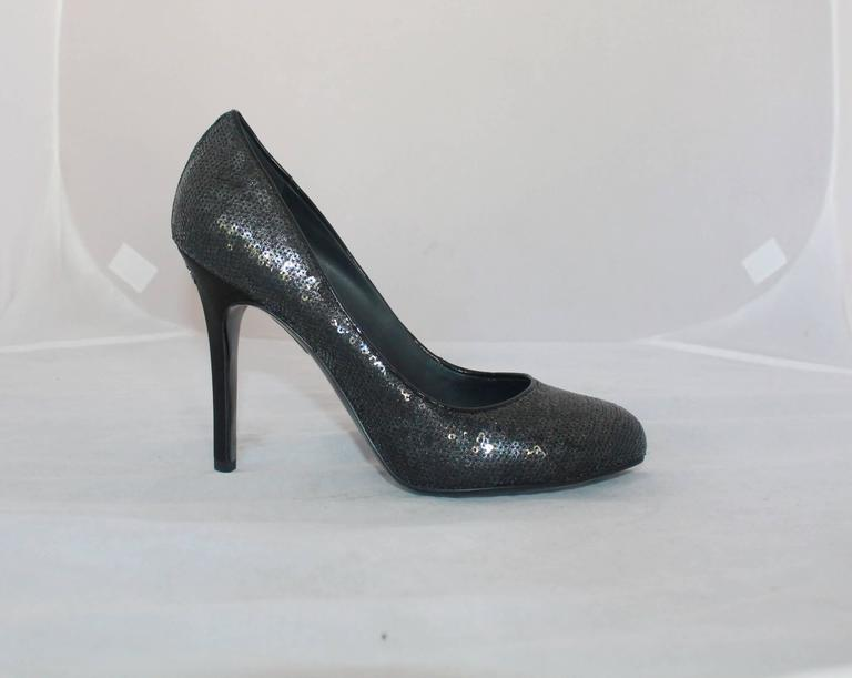 "Chanel Black Sequin Pumps w/ Quilted Interior - Never Worn - 40.  These exquisite pumps are absolutely beautiful with the entire exterior covered in black sequins.  They have a silver ""CC"" on the heel.  They are in perfect condition as"