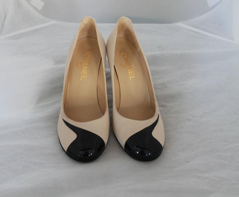 Chanel Champagne & Black Satin & Patent Pumps w/ Geometric Design - 38.5.  These beautiful pumps have a unique patent geometric design on the front and an elegant pearl on the inner side of the heel with a gold