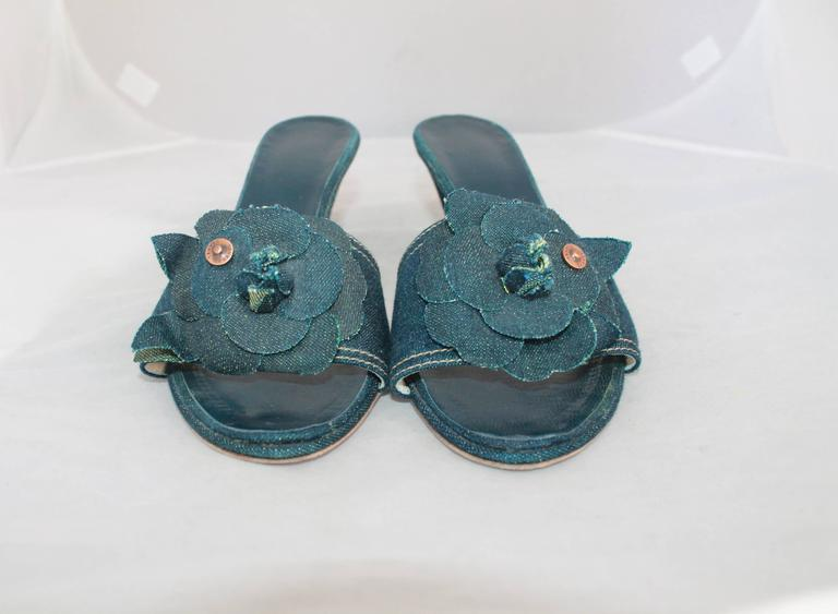 """Chanel Blue Denim Slides w/ Camellia & Chanel Rivet - 40.  These slides are in excellent condition with wear to the sole.  They are made of a denim material, as are the Camellias.  They have a copper-looking rivets with """"Chanel"""" on them, and """"CC"""""""