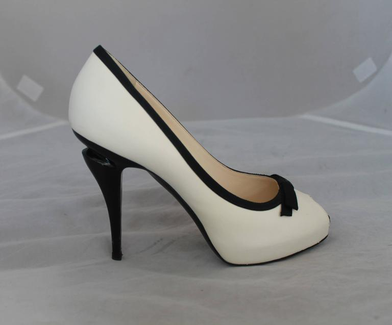 "Chanel Ivory & Black Lambskin Peep Toe Pumps w/ Black Ribbon Trim - 40.  These peep-toe pumps have a black ribbon trim with a front ""CC"" center bow.  It has a unique geometric as seen in Image 4.  They are in very good condition with a slight smudge"