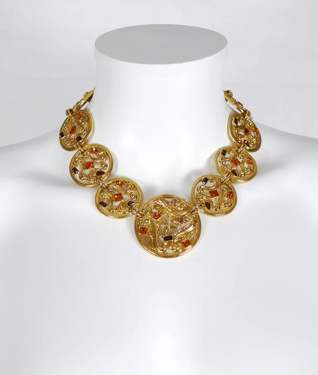 YVES SAINT LAURENT vintage gold toned medallion necklace featuring an openwork scroll design with crystal embellishement.  Lobster clasp closure with extension chain.  Embossed YSL Made in France on the clasp.  Indicative measurements : max. length
