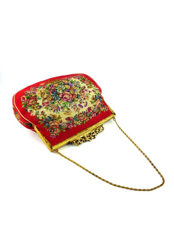 Gorgeous vintage floral design tapestry handbag.  This handbag features : - Tiara-style top closure.  - Gold tone hardware. - Chain handle. - Off-white leather lining. - 2 inner pockets.  Indicative measurements : total length (incl.