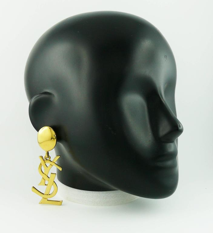 YVES SAINT LAURENT massive vintage gold toned iconic logo dangling earrings (clip on).  Rare and collectable item !  As seen on SAMANTHA JONES in SATC 2.  Marked YSL Made in France.  JEWELRY CONDITION CHART - New or never worn : item is in