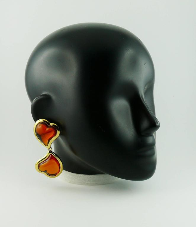 YVES SAINT LAURENT vintage dangling earrings (clip-on) featuring two orange resin cabochon hearts in a gold toned setting.  Marked YSL Made in France.  Indicative measurements : length approx. 7.5 cm (2.95 inches) / max. width approx 3.4 cm (1.34