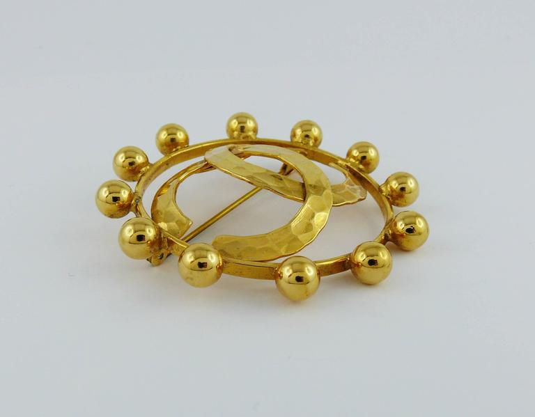 CHANEL vintage massive gold toned brooch featuring a large hammered CC monogram at center surrounded by a ring embellished with balls.  Marked CHANEL 2 5 Made in France. Collection year 1990.  Indicative measurements : diameter approx. 4.7 cm (1.85