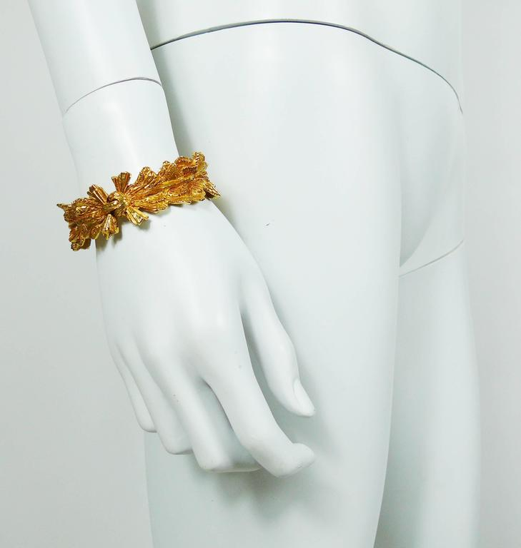 CHRISTIAN LACROIX vintage gold toned clamper bracelet featuring a textured ribbon and bow design with clear crystal embellishement.  Marked CHRISTIAN LACROIX CL Made in France.  Indicative measurements : circumference approx. 17.59 cm (6.93 inches)
