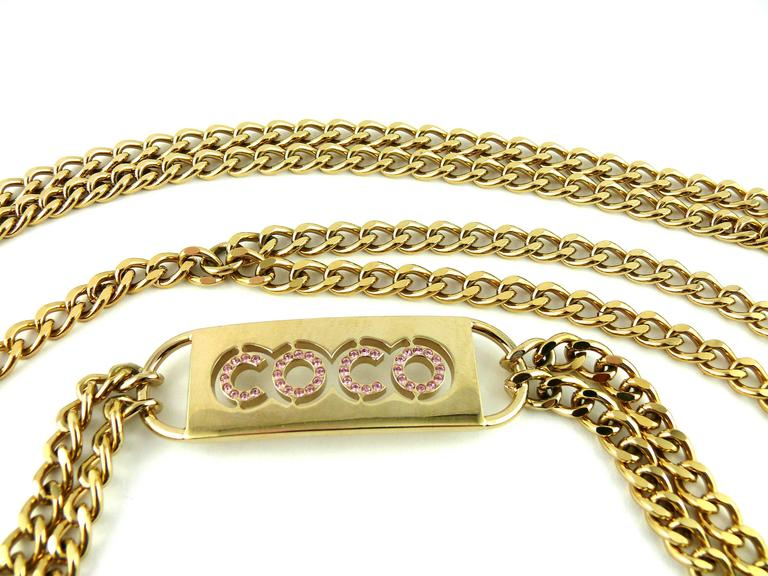 CHANEL gold tone double chain belt featuring a COCO ID tag with pink Swarovksi crystal embellishement.