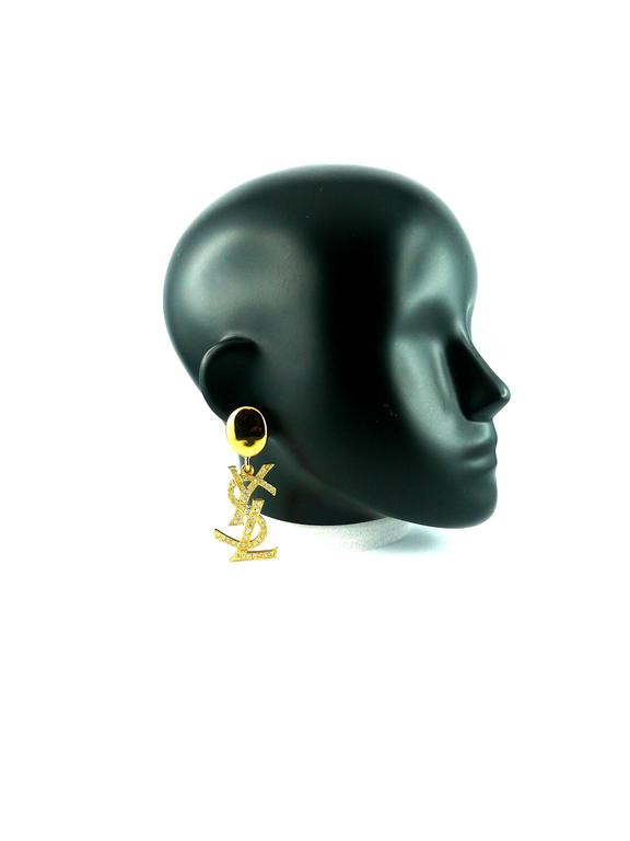 YVES SAINT LAURENT massive vintage gold tone iconic logo dangling earrings (clip on) with rhinestone embellishement.   Hard to find and collectable item !   Marked YSL Made in France.  Comes with YSL box.  JEWELRY CONDITION CHART - New or never worn