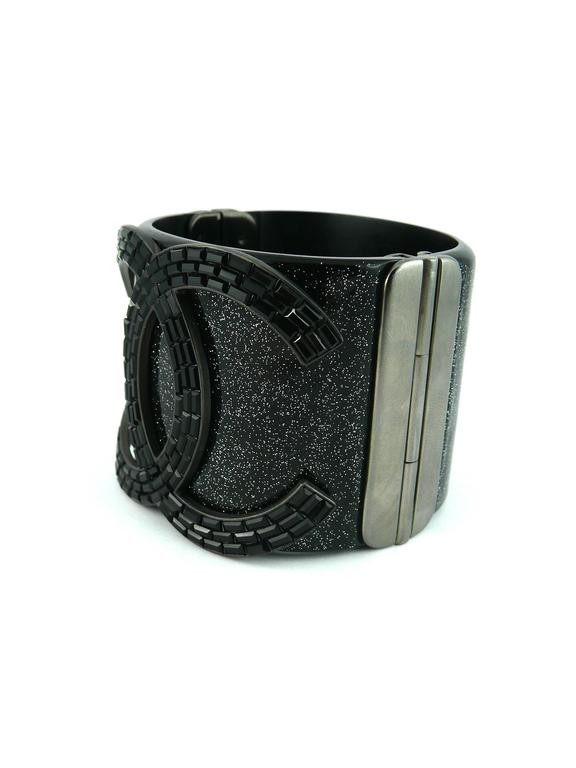 CHANEL rare glittering black resin cuff bracelet featuring a massive CC logo set with jet Swarovski crystal baguettes.  Spring / Summer Collection 2009.  Hinge clasp embossed with CC logo.  Stamped CHANEL 09 P Made in Italy.  Indicative