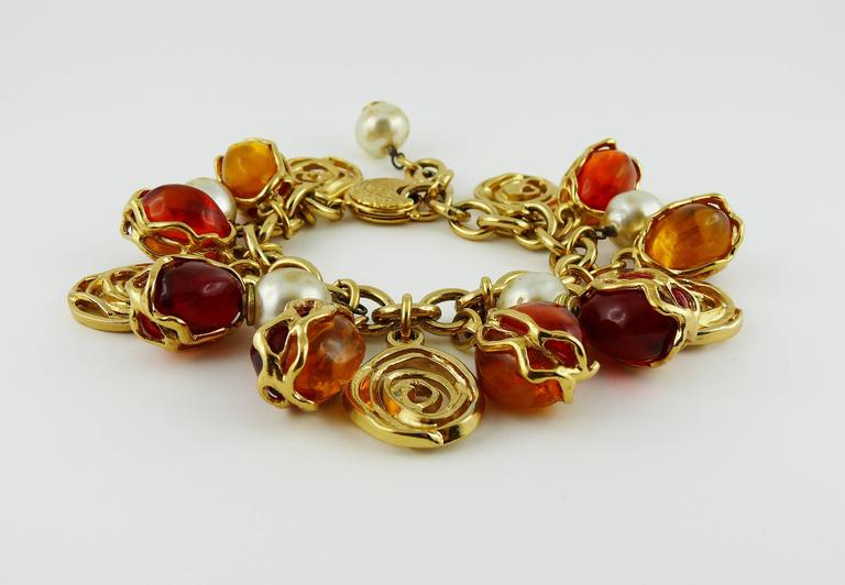 YVES SAINT LAURENT vintage chunky gold tone chain link bracelet featuring resin cabochons, spirals and faux pearls charms.  Embossed YSL Made in France on the clasp.  Indicative measurements : adjustable length approx. 16.50 cm - 19.50 cm (6.50