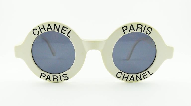 CHANEL extremely rare vintage 1990s white sunglasses with black CHANEL PARIS lettering.  Spring/Summer 1993 RTW collection (page 162, CHANEL CATWALK, Patrick Mauries, Thames & Hudson).  Signed CHANEL on the inside temple. Made in Italy 01945