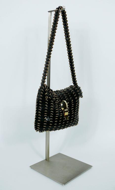 PACO RABANNE vintage shoulder bag from the 1970s featuring black rodhoid discs and gold toned harware.  Marked PACO RABANNE Paris - Production R I C A F Italy.  Indicative measurements : height incl. strap approx. 42 cm (16.54 inches) / height excl.