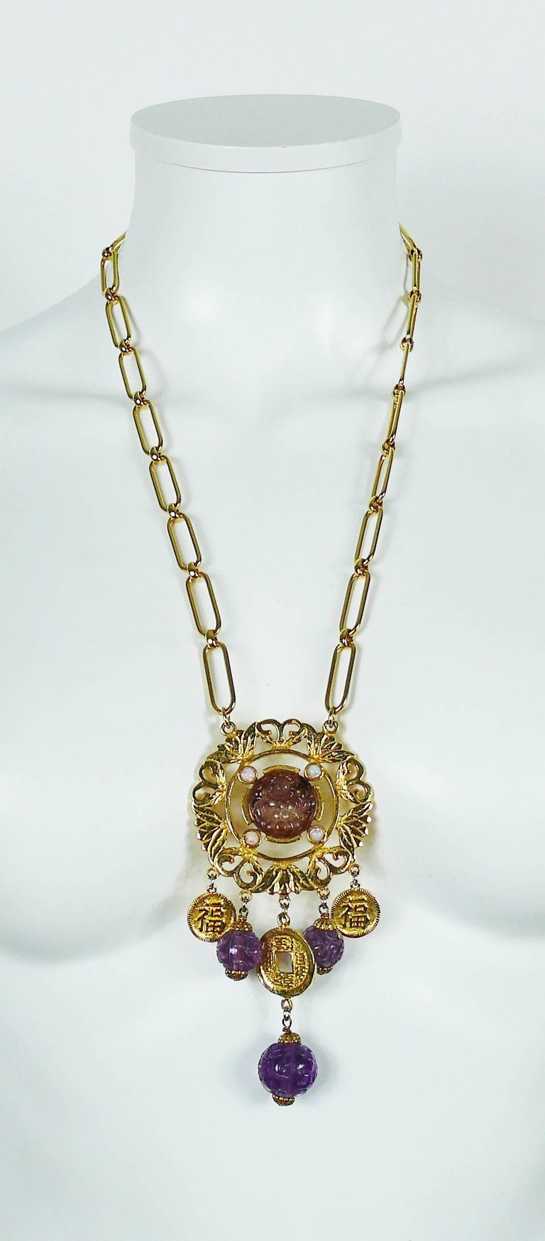 CADORO vintage gold toned necklace featuring a Chinese inspired openwork disc pendant with purple resin ornaments, faux moonstones and coin charms.  Marked CADORO.  Spring clasp closure.  Indicative measurements : chain length approx. 63 cm (24.80