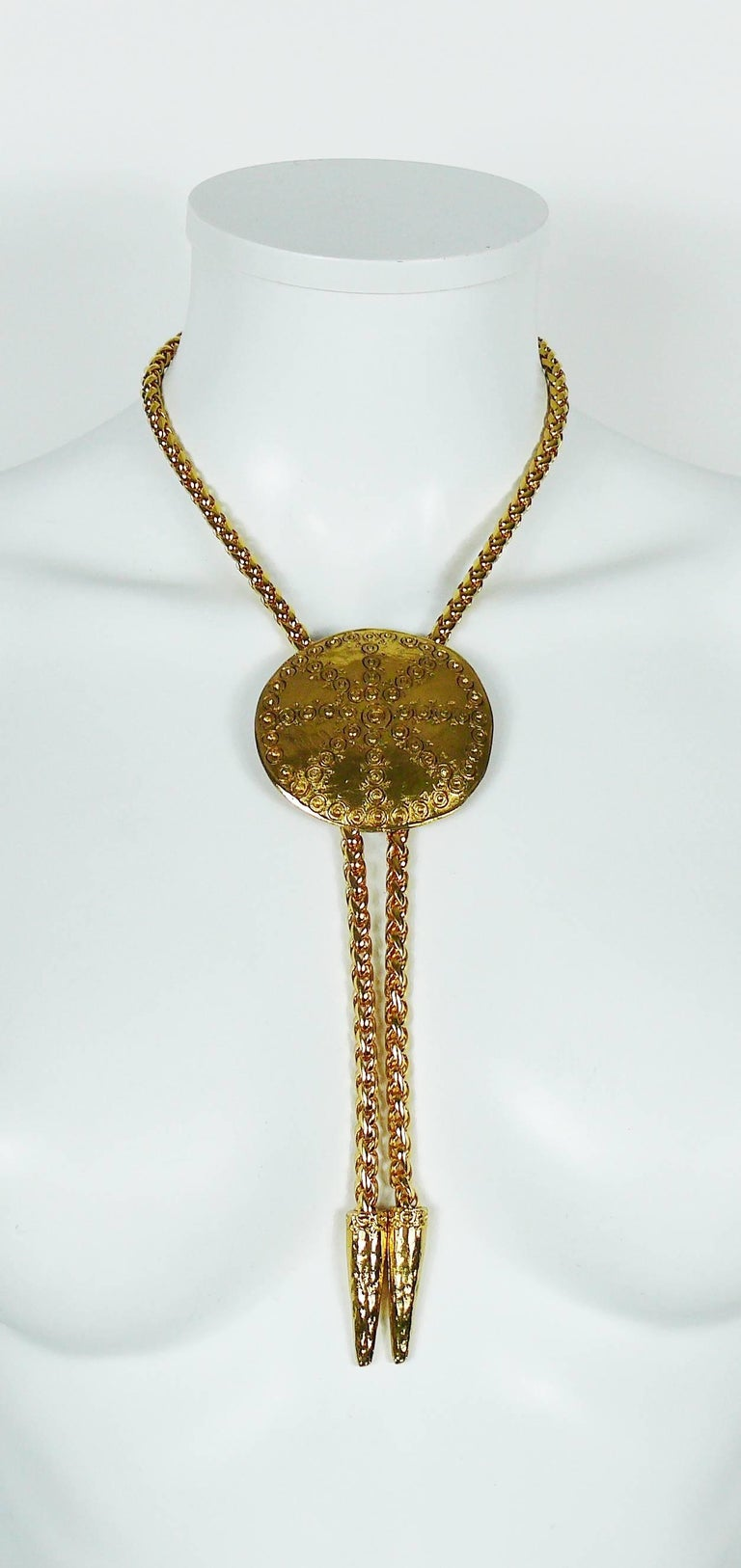 YVES SAINT LAURENT vintage gold toned lariat necklace featuring a large ethnic disc.  The height of the disc is adjustable.  Embossed YSL Made in France.  Indicative measurements : max. length worn (including tassels) approx. 33 cm (12.99 inches) /