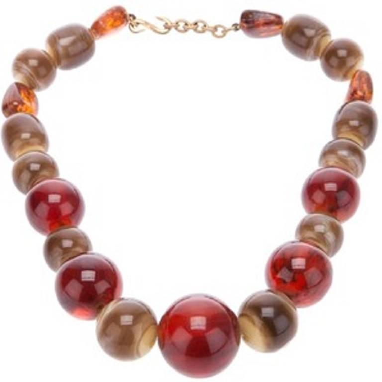 YVES SAINT LAURENT early necklace featuring faux amber and faux horn graduated resin ball beads.  Created by the French parurier ROGER SCEMEMA in the 1970s.  S hook closure.  Embossed YSL France on the hook.  Indicative measurements : total length