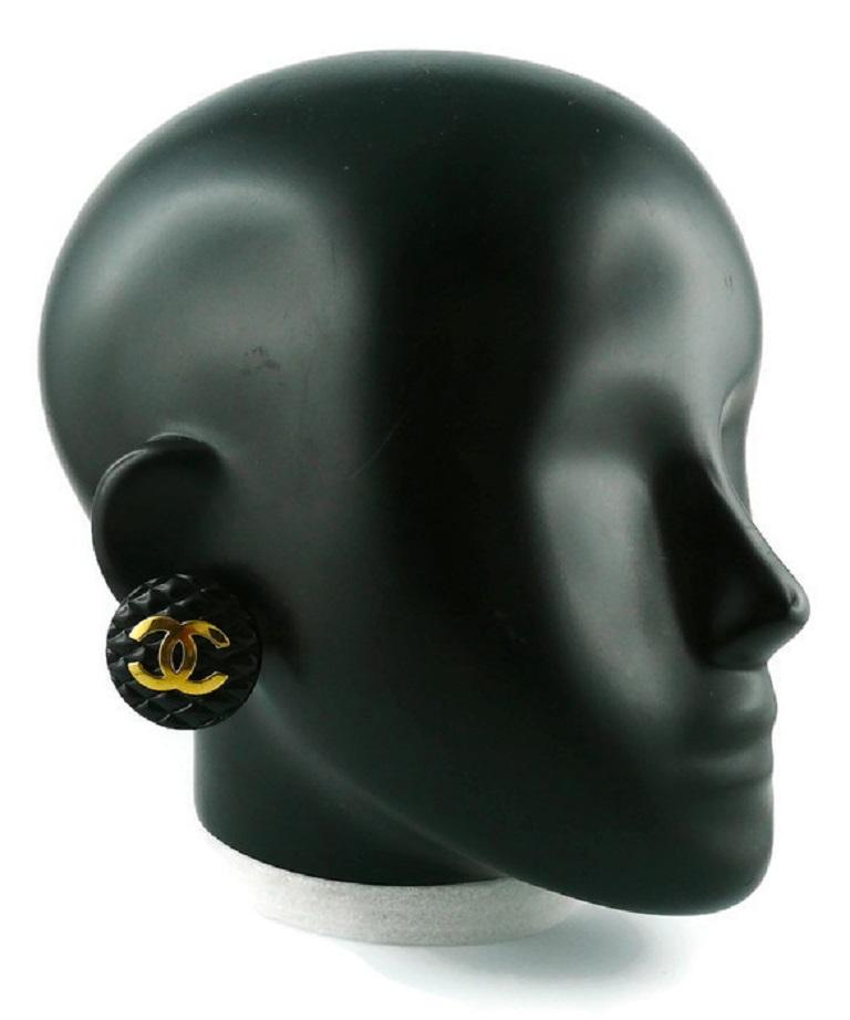 CHANEL vintage 1994 large quilted black resin clip-on earrings featuring a gold toned CC monogram.  Embossed CHANEL 2 9 Made in France.  Indicative measurements : diameter approx. 3.4 cm (1.34 inches).  JEWELRY CONDITION CHART - New or never worn :