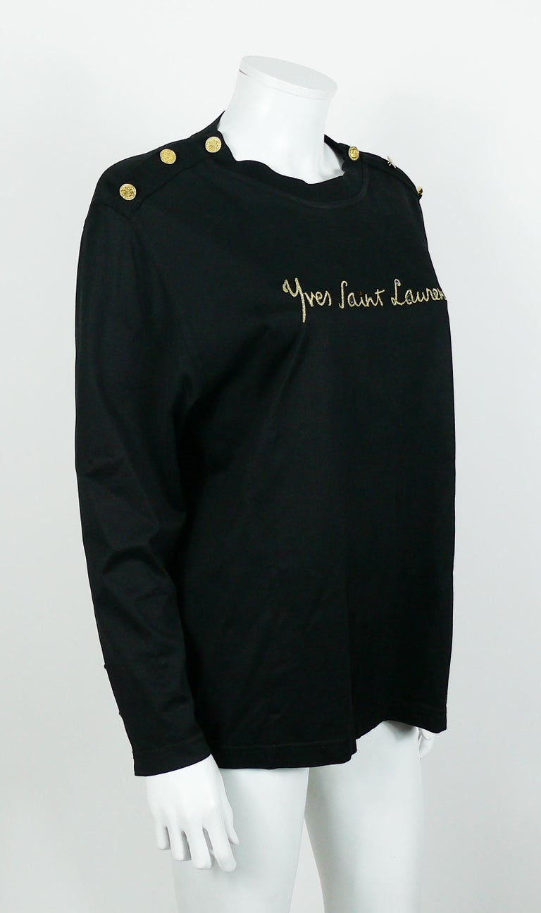 Yves Saint Laurent Variation vintage black top featuring a gold embroidered cursive signature embellished with multicolored resin crystals.  Coat of arms gold toned buttons on shoulders and cuffs.  Label reads YVES SAINT LAURENT VARIATION.  Size