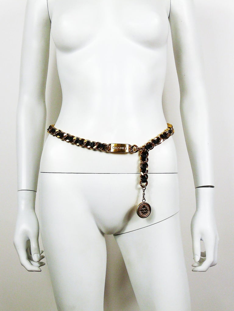 CHANEL vintage gold toned chain belt with intertwined black leather, ID plate embossed CHANEL and double sided CC medallion coin charm.  Hook closure. Adjustable length.  Can be worn as a necklace.  Embossed CHANEL on the hook.  Indicative