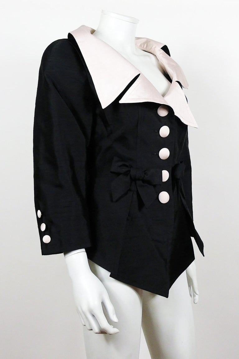 CHRISTIAN LACROIX vintage 18th Century inspired black jacket featuring an oversized powder pink asymetric collar and bow details.  This jacket features : - 18th Century inspired style. - Ovesized powder pink asymetric collar. - Two bow on front. -