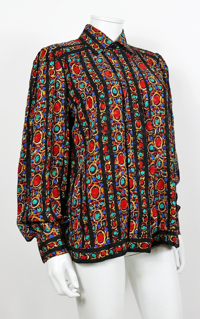 YVES SAINT LAURENT vintage iconic jewel print blouse.  This shirt features : - Gorgeous opulent multicolored jewel print with black accents. - Classic collar. - Long sleeves. - Hidden front buttoning. - Black buttons on cuffs.  Label reads YVES