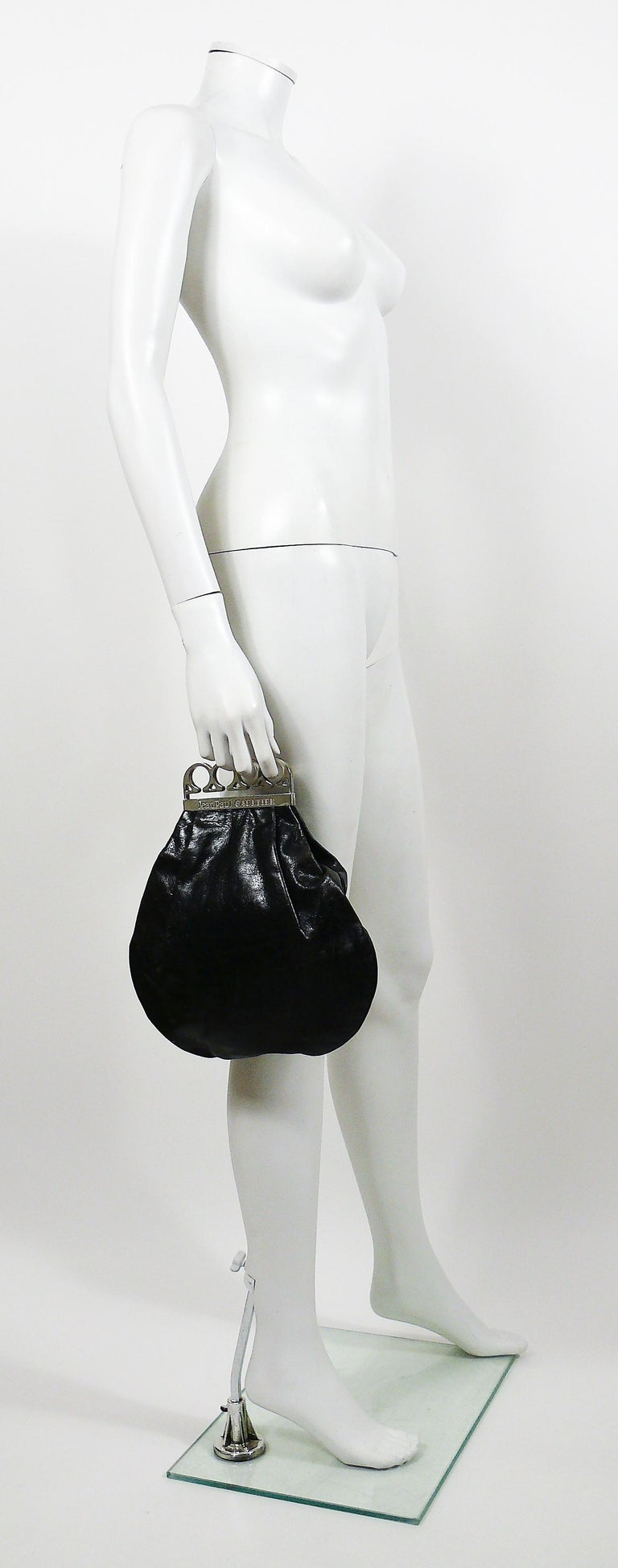 JEAN PAUL GAULTIER vintage rare black distressed leather knuckle duster clutch.  This clutch features : - Black distressed leather body. - Polished silver toned knuckle duster handle embossed JEAN PAUL GAULTIER. - Magnetic closure. - One inner