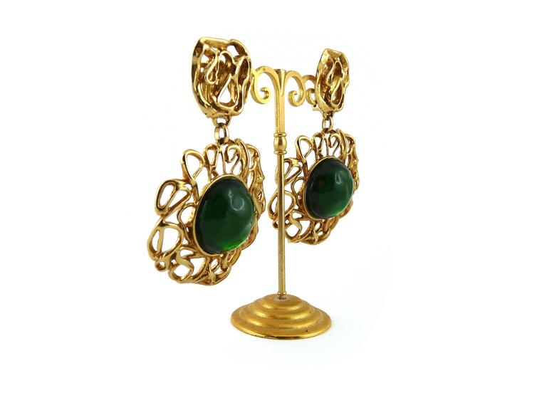 YVES SAINT LAURENT vintage massive dangling earrings, created in the ateliers of French parurier Robert GOOSSENS.  Gold tone interlaced metal embellished with a massive emerald resin cabochon.  Marked YSL Made in France. Numbered A0.  Comes