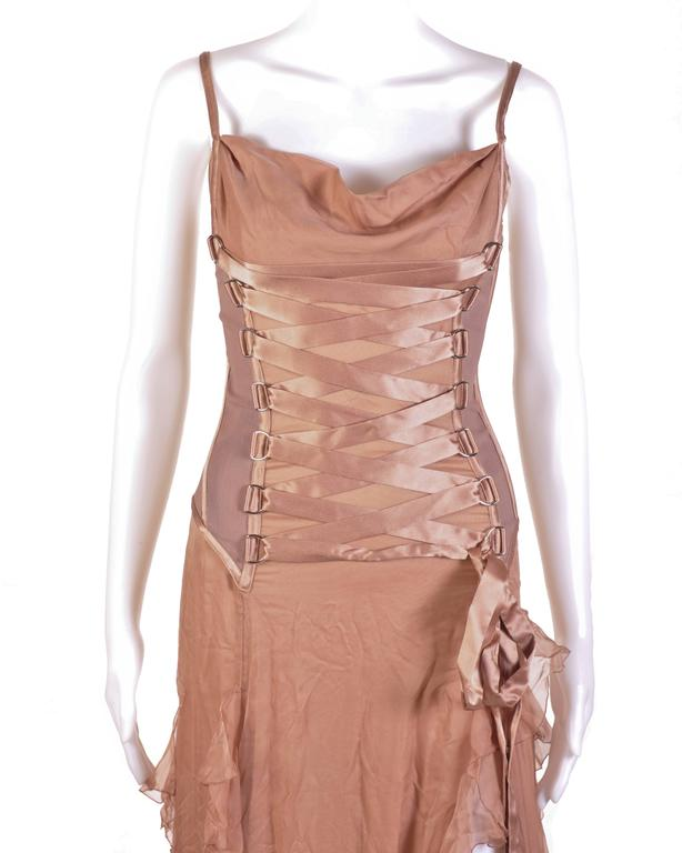 VERSACE Nude Corset Long Dress  Look every bit the fairy tale princess in this romantic Versace gown. This spaghetti strapped dress is fashioned with nude, silk chiffon and a corset-styled bust. The corset is medium weight, fully lined, boned at the