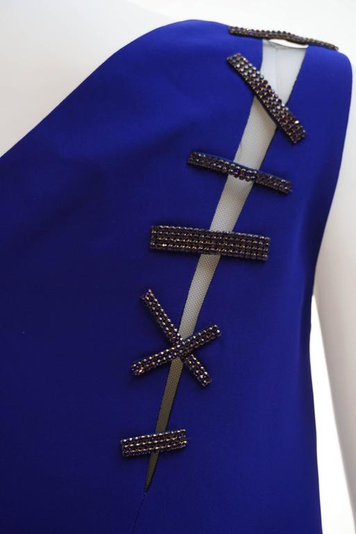 VERSACE   Cut-out embellished crepe dress  This cobalt crepe dress is a standout creation.   The sleek shift silhouette is slashed to reveal slices of skin, and repaired with glittering Swarovski crystal stitches.   Fully lined  Hidden zip
