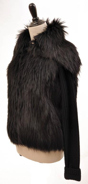 This sweater from Versace features full-length sleeves,two pockets, and oversized collar.  95% wool, 5% elastine with 100% raccoon fur  Made in Italy  IT sizes: 42 and 44  Retail price is $6,125.00  New, with tags.  Due to restrictions, this item
