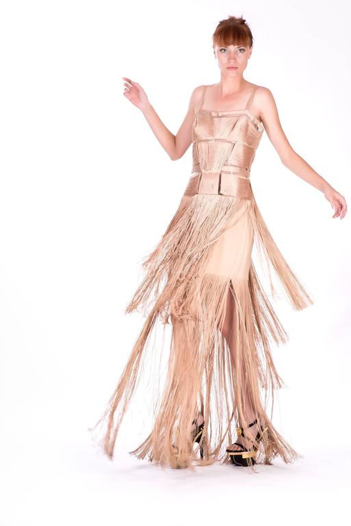 Showcasing Versace's penchantfor spotlight-stealing designs, this nude gown commands attention. Spaghetti straps keep the slimming bustier silhouette in place as it encapsulates your curves. The best part of this design is its matching