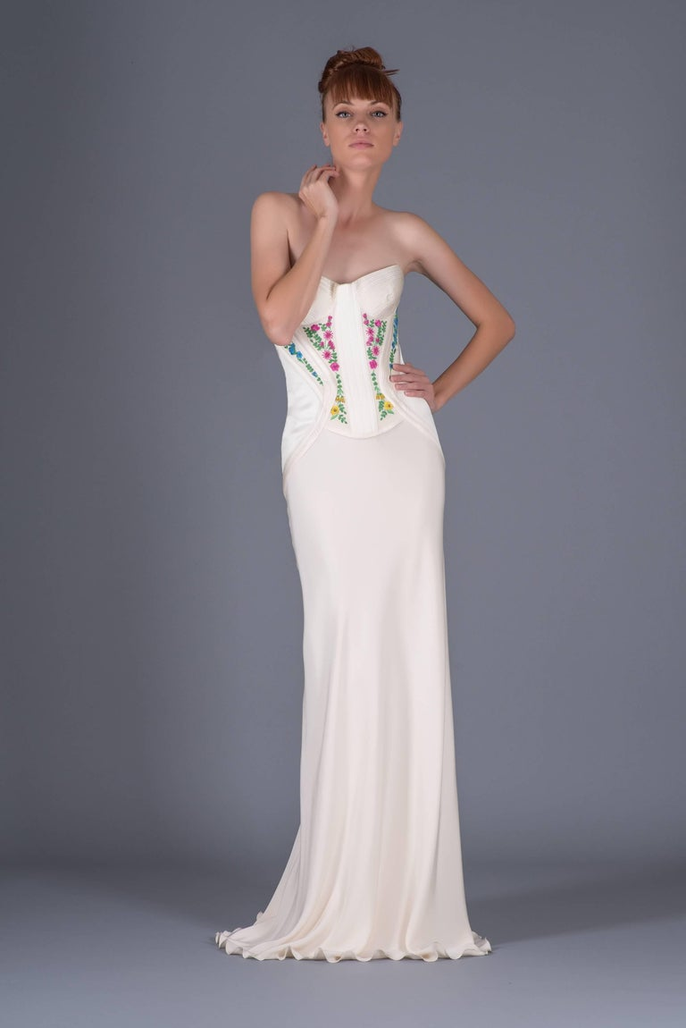 Revived from Gianni Versace's archive is this gorgeous, floor-skimming, dress. Donatella brought back this design that originally was part of Gianni's Atelier line in 1995. Adorned with colorful, floral embroidery this white dress is simply