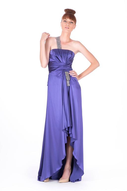 Make an eye-catching entrance with this regal Versace creation. Fashioned from delicate silk this gorgeous dress will make you feel like a modern-day Grace Kelly. A floor-length gown with a high-low hem is a dreamy vision in elegant purple. Silver