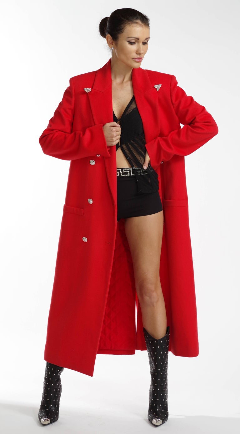 VERSACE Long coat in red  This wool cashmere coat from Versace features a crystal-tipped notch lapel, full-length sleeves, slip front pockets, and a single vent at back.  Double breasted medusa logo button fastenings  90% wool, 10% cashmere Quilted