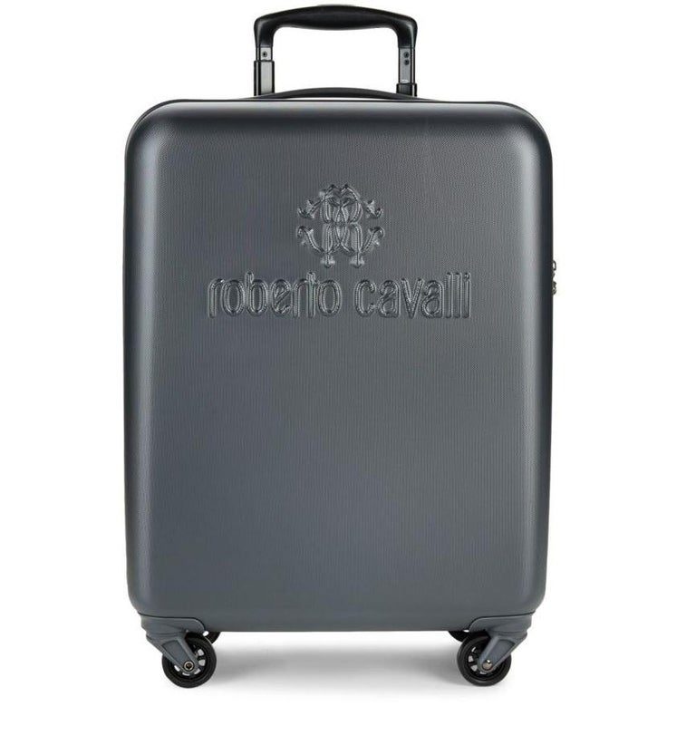 Roberto Cavalli  Logo Hardshell Suitcase. Available in two colors - Platinum and Black.   Iconic logo adds a luxurious flourish to this streamlined suitcase.  Top handle Zip-around closure Silvertone hardware Side lock Four-wheel system One inside