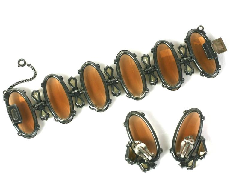 Elsa Schiaparelli's massive bracelet and ear clips of large smokey topaz top facet crystals with citrine and Aurora Swarovski crystal spacers. Extremely striking combination of colors and scale, set into antique silvered metal. 1950's USA,
