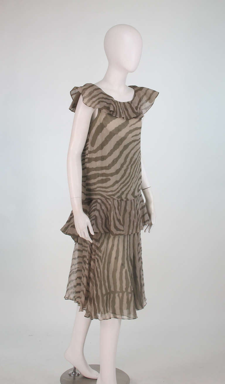 1920s inspired...1980s Bruce Oldfield zebra metallic silk chiffon flutter dress...Sheer silk chiffon zebra fabric is woven with silver metallic squares...Two piece dress features a slip on tunic top that is sleeveless with a ruffle neckline, semi
