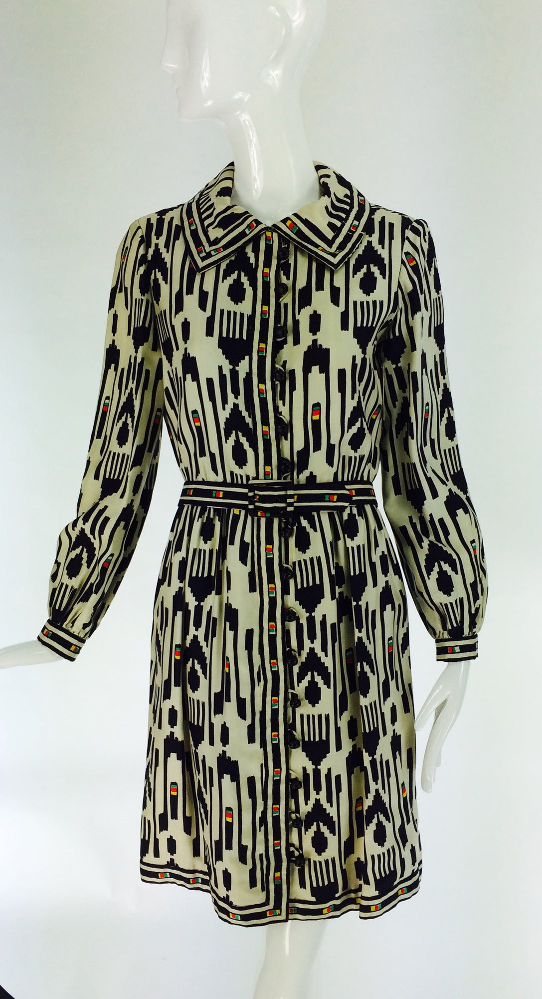 Silk twill ikat print shirt waist/coat dress dress in black and cream with pops of yellow, green and red...Tribal influenced design on a classic dress that could be worn as a lightweight coat...Long sleeve dress closes at the front with loop and