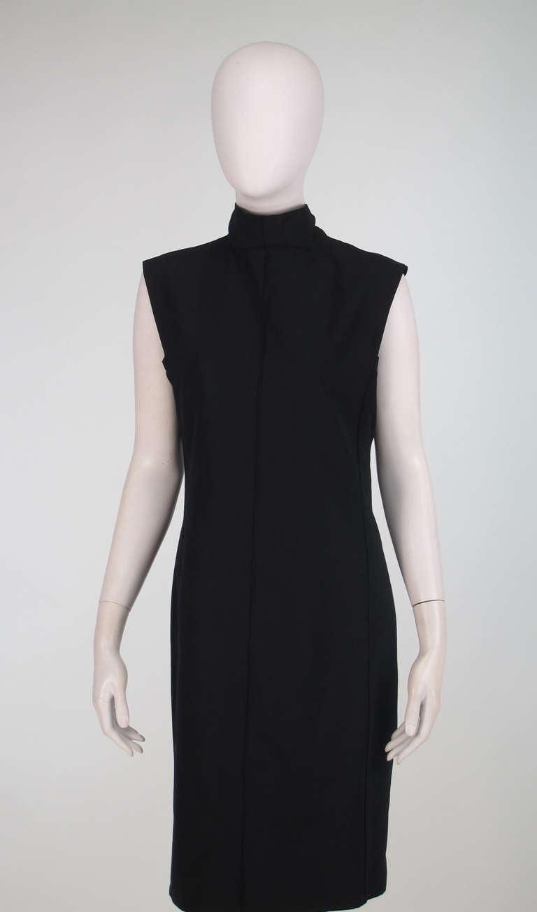 Yves St Laurent black bow back sheath dress...Chic dress in textured black silk is sleeveless and has an extended shoulder...Slightly fitted with seamed panels...The neckline features a banded collar that forms long ties that can be worn as a bow at